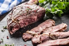 Freshly grilled tomahawk steak on slate plate with salt pepper rosemary and parsley herbs. Sliced pieces of juicy beef steak.  stock photos