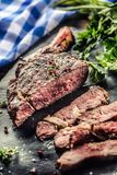 Freshly grilled tomahawk steak on slate plate with salt pepper rosemary and parsley herbs. Sliced pieces of juicy beef steak.  royalty free stock photo