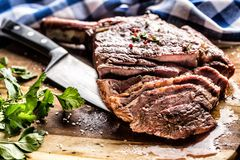 Freshly grilled tomahawk steak on slate plate with salt pepper rosemary and parsley herbs. Sliced pieces of juicy beef steak royalty free stock images