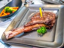 Freshly grilled Tomahawk steaks, herbs and spices on black plate. Top view with copy space for your text. stock image