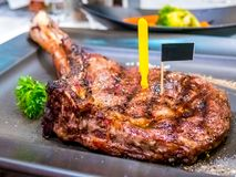 Freshly grilled Tomahawk steaks, herbs and spices on black plate. Top view with copy space for your text. stock photos