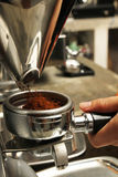 Freshly grinded coffee being emptied onto coffee holder. Barista obtaining freshly grinded coffee powder Royalty Free Stock Image