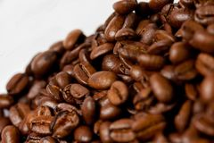 Freshly ground coffee beans roasted with fruits of coffee plant, on white background stock image