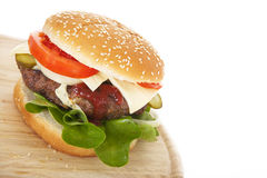 Freshly hamburger on wooden plate Royalty Free Stock Photography