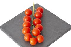 Freshly harvested cherry tomatoes on a stone plate. Fresh and ripe tomatoes on a black slate plate Royalty Free Stock Image