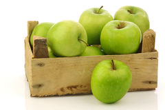 Freshly harvested Granny Smith apples. In a wooden crate on a white background Royalty Free Stock Images