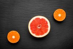 Freshly harvested grapefruit and mandarin on stone background Royalty Free Stock Photography