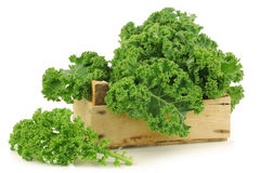 Freshly harvested  kale cabbage in a wooden crate. On a white background Royalty Free Stock Photos