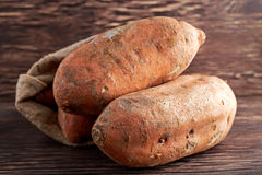 Freshly harvested organic sweet potatoes in a burlap bag on wooden table. Royalty Free Stock Photos