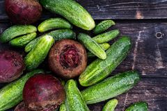 Freshly harvested pickling cucumbers and beetroots on dark rusti Royalty Free Stock Photos