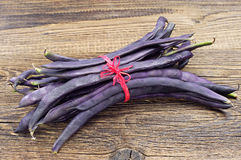 Freshly harvested purple string beans. Tied with red ribbon on wooden table Royalty Free Stock Images