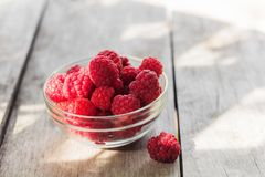 Freshly harvested raspberries in a glass bowl. On  rustic wooden table Royalty Free Stock Photography