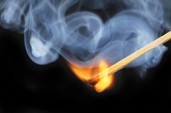 Freshly ignited match. Flame with swirling blue smoke against a black background Royalty Free Stock Photo