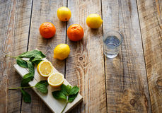 Freshly lemons and oranges with glass water on wooden boards Royalty Free Stock Images