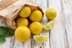 Freshly lemons in paper bag on white wooden table Stock Images