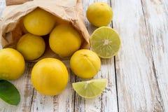 Freshly lemons in paper bag on white wooden table Royalty Free Stock Image