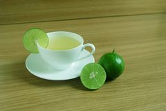 Freshly Lime juice in a white cup. On wooden floor stock photos