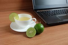 Freshly Lime juice in a white cup, and laptop. On wooden floor royalty free stock photos