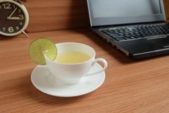Freshly Lime juice in a white cup, and laptop. On wooden floor stock photography