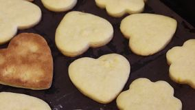 Freshly made biscuit cookies lie on a baking sheet and cool. Cookies in the shape of a heart and flowers. One is upside down, the. Ruddy side of the cookie is stock video