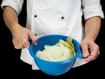 Freshly made boiled parted cabbage in a colander, held by chef i Stock Photo