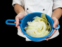 Freshly made boiled parted cabbage in a colander, held by chef i Stock Photography