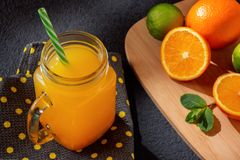 Freshly made citrus juice from oranges, grapefruit and lime in a jar-mug with a straw on black table royalty free stock image
