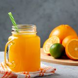 Freshly made citrus juice from oranges, grapefruit and lime in a jar-mug with a straw on gray table stock photography
