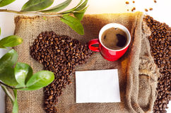 Freshly made coffee next to cooffee beans made in shape of South America Stock Photography