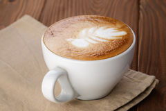 Freshly made cup of cappuccino with leaf art Stock Image
