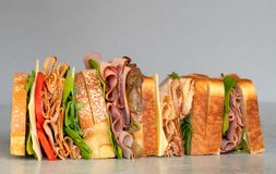 Freshly made deli style sandwich with lettuce, several different kinds of vegetables, tomatoes, cheese, meats similar to ham,. Chicken or turkey. Great for royalty free stock photography
