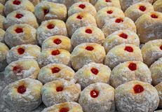 Freshly made donut center filled with strawberry jam and topped. With icing sugar in tray Stock Images