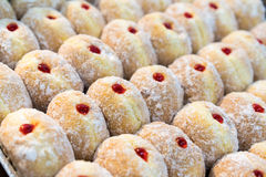 Freshly made donut center filled with strawberry jam. And topped with icing sugar in tray Stock Image