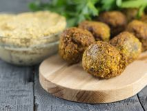 Pasta tahina in a glass bowl and falafel on a cutting Board on a wooden table. royalty free stock photos
