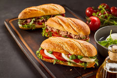 Freshly made gourmet sandwiches on wooden tray. With tomatoes on vine, basil and olive oil Stock Images