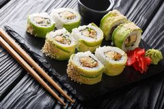 Freshly made Japanese rolls with avocado, omelette, sesame and cucumber close-up on a plate. horizontal royalty free stock image