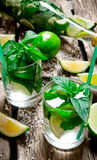 Freshly made mojito in glass and the bottle with mint and lime, sugar and rum. On a wooden table. Stock Photography