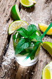 Freshly made mojito with mint and lime, sugar and rum. On a wooden table. Royalty Free Stock Image