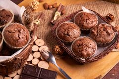 Freshly made muffins in a basket with walnuts, almond nuts, dark choc olate stock photography