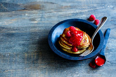 Freshly made pancakes. Close up of freshly made pancakes with raspberry jam and fresh raspberries in rustic wooden bowl for breakfast over vintage background Stock Photo