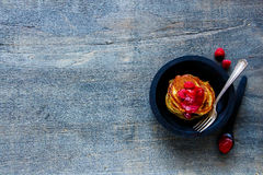 Freshly made pancakes. Delicious freshly made pancakes with raspberry jam and fresh raspberries in rustic wooden bowl for breakfast over vintage background, top Royalty Free Stock Image