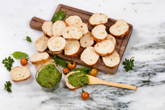 Freshly made pesto and sliced bread on wooden server Stock Photos