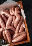 Freshly made raw butchers sausages in skins with herbs. royalty free stock photography