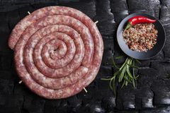 Freshly made raw spiral sausages in skins on a black background of charcoal. A stock images