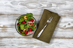 Freshly made salad with raspberries on white table. Overhead view of freshly made salad in glass bowl with fork and napkin on white wooden table Stock Photo