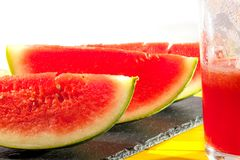 Freshly made vegan watermelon drink. Thirst quenching summer cru. Sh with fruit slices and half drunk glass of juice. Close up against white background Stock Image