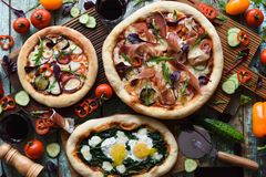 Freshly made yummy pizza party. Flatlay of puffy pizzas with pancetta, aubergines, spinach, eggs, bell pepper and arugula served royalty free stock photo