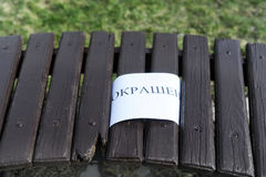 A freshly painted bench in the park with a caution sign. Closeup royalty free stock photo
