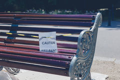 Freshly painted bench with sign. A freshly painted bench in the park with a caution sign royalty free stock image