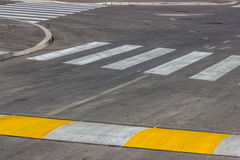 Freshly painted crosswalk and speed bump. For slowing traffic near school. Selective focus Royalty Free Stock Image